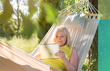 A woman on her iPad, lounging in a hammock